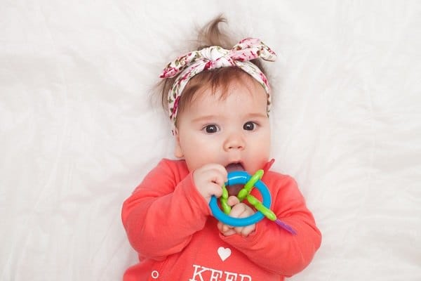 5 months old lovely baby portrait on white with teether toy